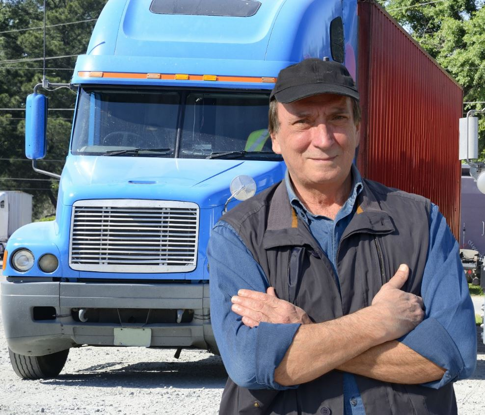 Driver standing with hands folded in front of a blue truck.