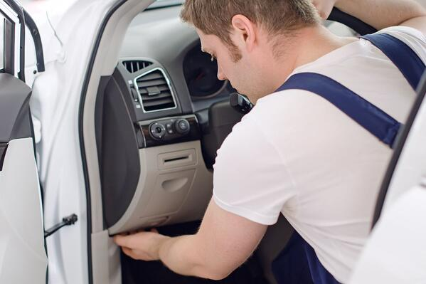 Mechanic covertly installing fleet tracking software.