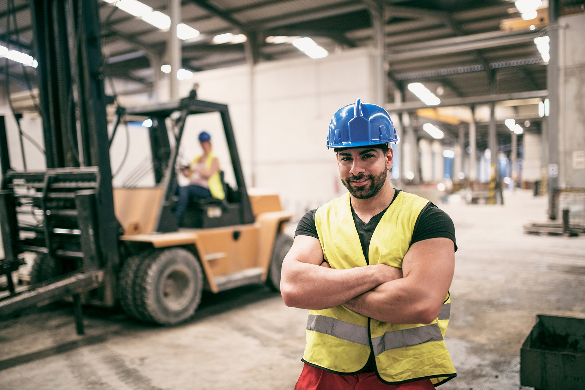 Trades worker standing with arms crossed, smiling.