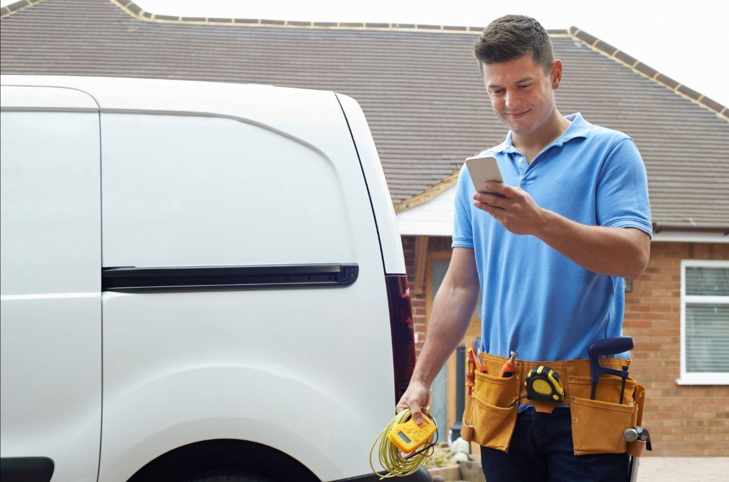 Tradesman looking at his mobile phone, smiling.
