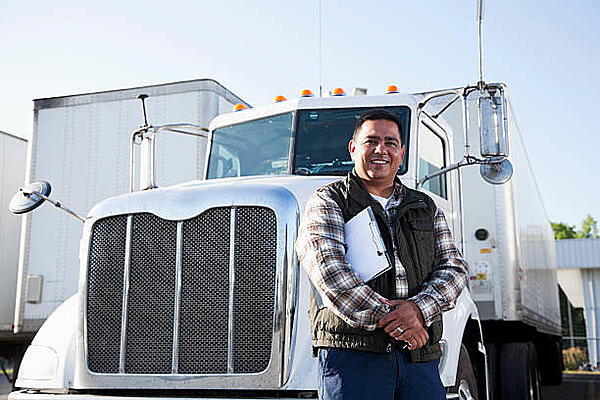 Truck driver standing in front of the truck, holding a clipboard.