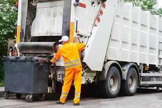 Waste Removal Vehicle With Worker