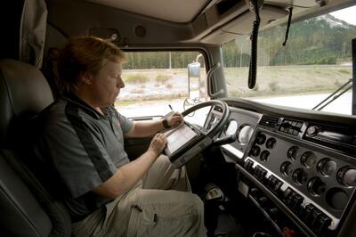 Truck driver filling out his daily log