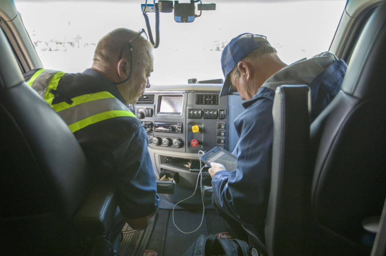 Man looking at a mobile device in the passenger seat, with truck driver looking over.-1