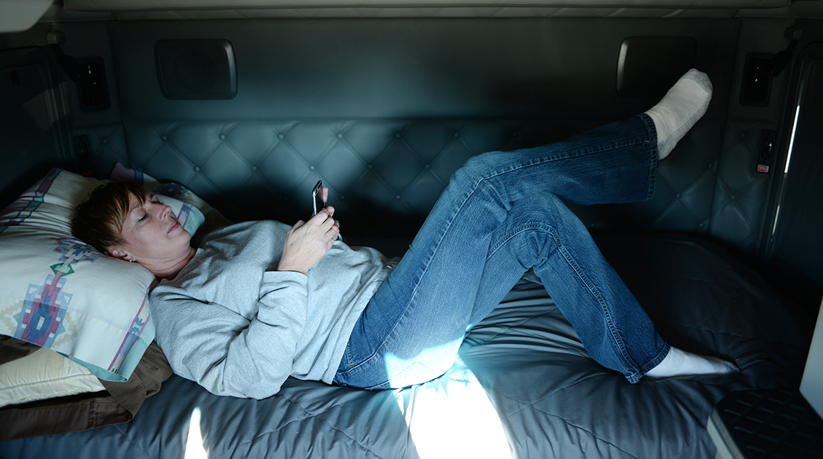 A woman relaxing in a sleeper berth.