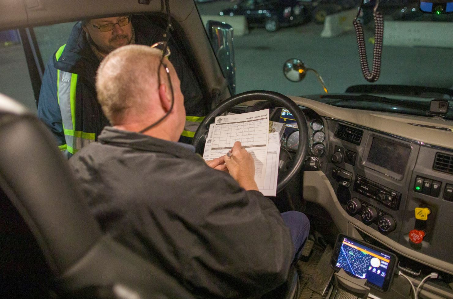 Truck driver filling out paper work.