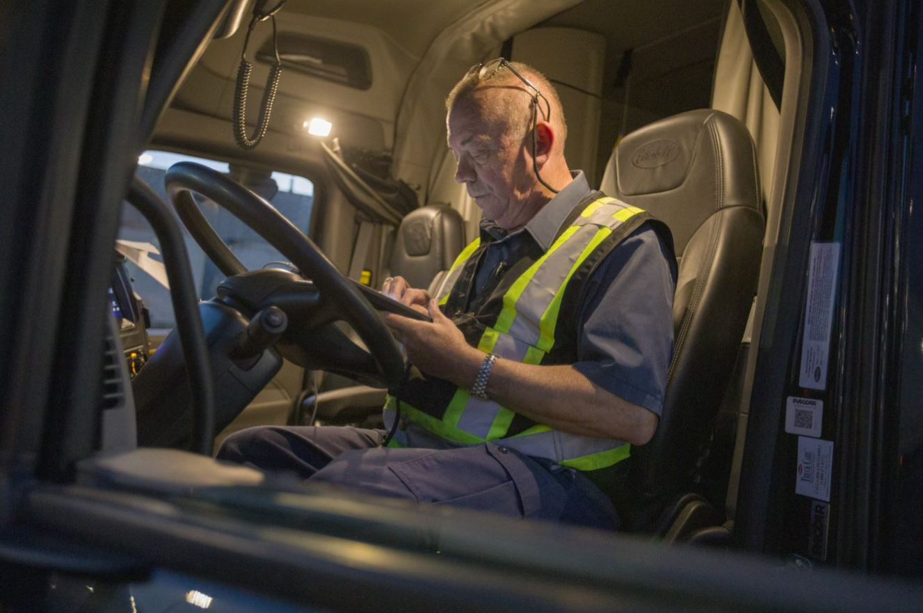 Truck driver in cabin looking at mobile device.